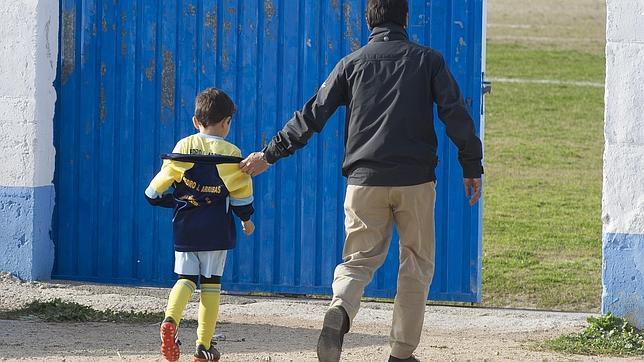 Un padre acompaña a su hijo a un partido de fútbol